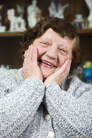Happy elderly woman holding hands on face and laughing photo