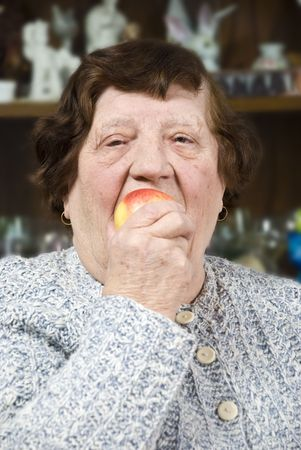 Elderly woman eating an apple concept of healthy lifestyle photo