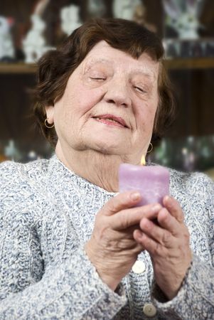 Older woman holding a big candle light and looking down while praying on her home Stock Photo - 6385080