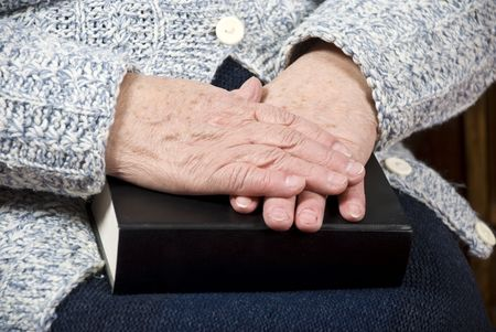 Elderly woman hands resting on a bible photo