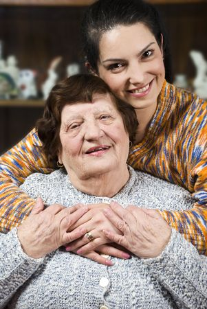 octogenarian: Granddaughter giving a hug to her grandma and both smiling and holding their hands together Stock Photo
