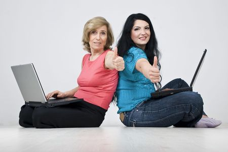 Two smiling women ,mother and daughter sitting on white wooden floor in  house,stand back to back  each one uses laptop  and giving thumbs up Stock Photo - 6825604