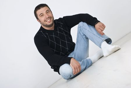 Young smiling man sitting on white wooden floor  in house photo