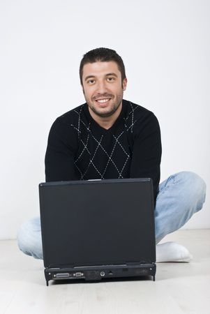 Smiling happy young man sitting on white wooden floor and using a laptop  photo