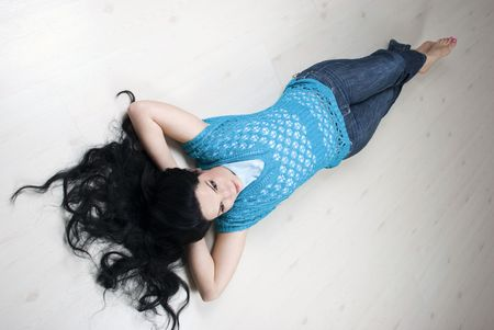 Top view of beautiful brunette with long hair lying down with hands under her head and relaxing on white wooden floor in new house photo