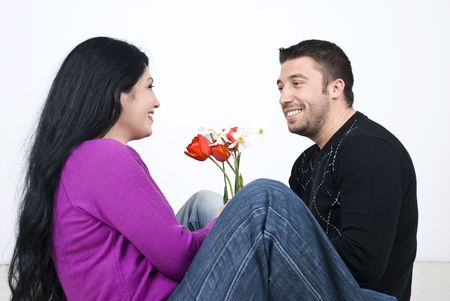 pullovers: Couple  sitting on wooden floor face to face and looking each other ,in their new house  and having a funny conversation while man giving her wife flowers to celebrate  and laughing together