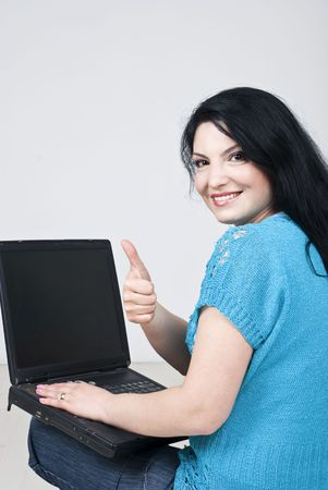 Happy woman sitting on white wooden floor using laptop blank screen and giving thumbs up ,rear view photo