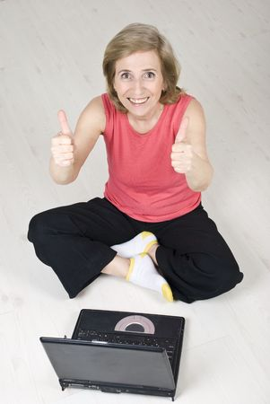 Top view of senior woman sitting on wooden floor with legs crossed giving thumbs up and using laptop  photo