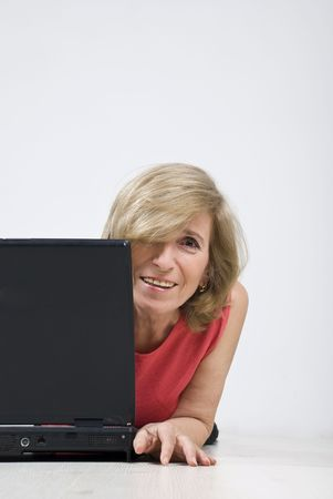 Portrait of blond mature woman hidden half behind laptop smiling for you,copy space for text message in right part of image photo