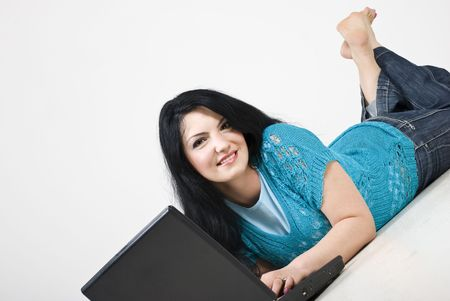 Smiling brunette woman lying down on white wooden floor and using laptop at home photo