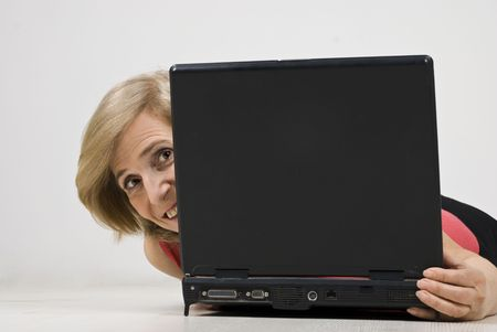 Smiling mature woman hiding behind laptop  and lying down on wooden floor photo