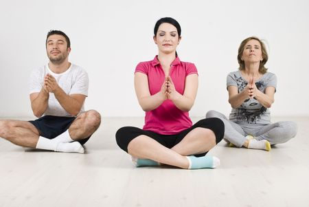 Three members of a family doing yoga on wooden floor in their home photo