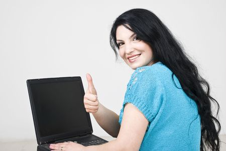 Beautiful woman using laptop  while sitting on floor and giving thumbs up,rear view photo
