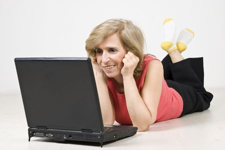 Senior woman lying down on white wooden floor and using a laptop photo
