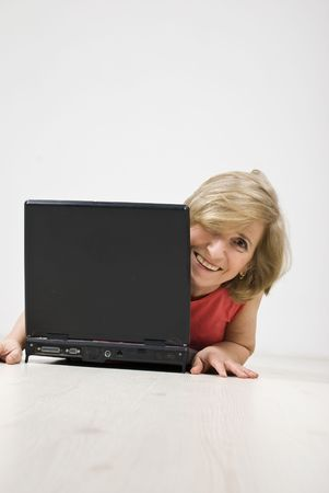 Senior woman laughing and looking behind a laptop while lying down on wooden floor photo