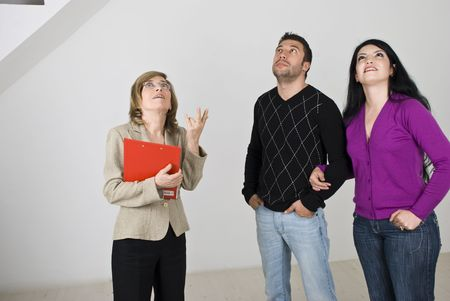 Young couple having a meeting with a senior estate agent and she showing them a new house,they all looking up at something photo