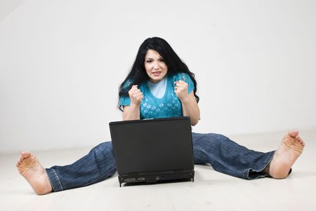 strained: Stressed woman expecting something on her laptop or hoping to not crash and sitting on floor with all body strained