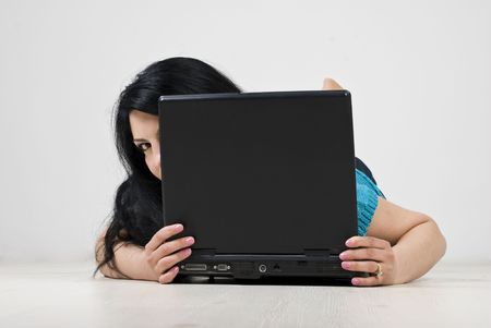 Young woman lying down on wooden floor , hiding  and looking behind laptop photo