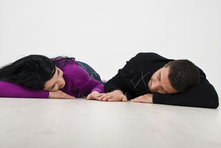 Young couple lying down on white wooden floor face to face and holding hands in their new house photo