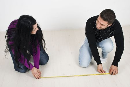 sitting on floor: Happy couple just  moved in new home and they planning and measuring on floor  having fun and laughing togehter