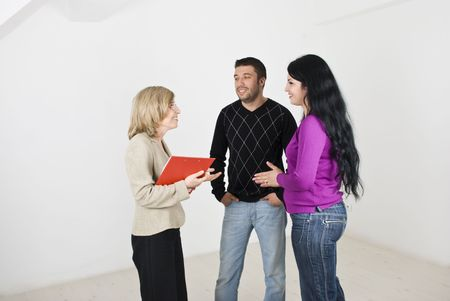 A real estate agent  senior woman trying to sell a new house to a young couple and having a conversation with them photo