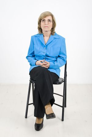 Single senior business woman sitting on chair at conference listening and looking serious photo