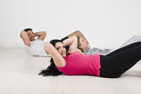 sit ups: Active happy family  lying on wooden floor doing sit ups for flat abs ,couple looking to camera and smiling  Stock Photo