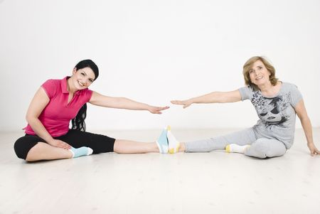 Active happy two women ,young and older training together on wooden floor photo