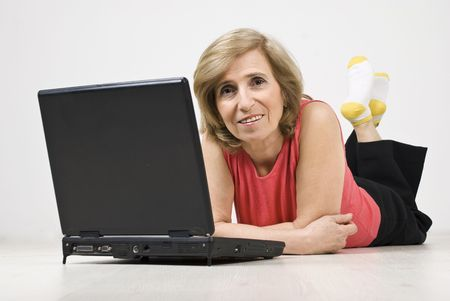 Mature woman lying down on wooden floor with legs up and using laptop photo