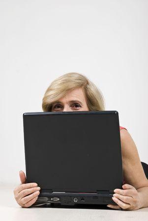 Senior woman hiding behind laptop and having fun photo