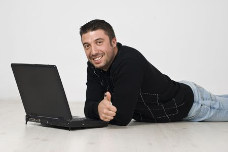 Successful happy man lying down on floor using laptop and giving thumbs up photo