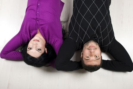 Happy young couple lying down on wooden floor with their hands under head,top view photo