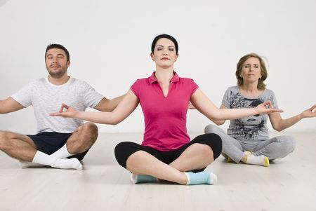 Group of people  doing yoga and sitting on floor in lotus position photo
