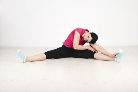 Woman doing fitness and sitting on white laminate flooring photo