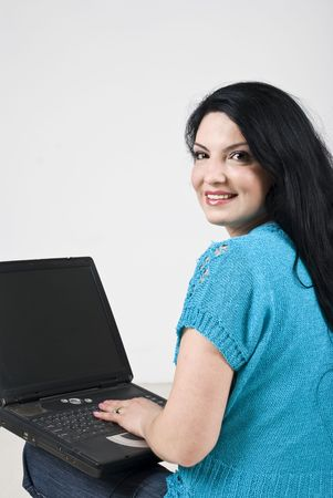 Happy young woman using laptop  ,smiling and looking over shoulder photo