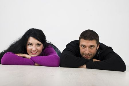 Smiling young couple lying down on floor and looking you photo