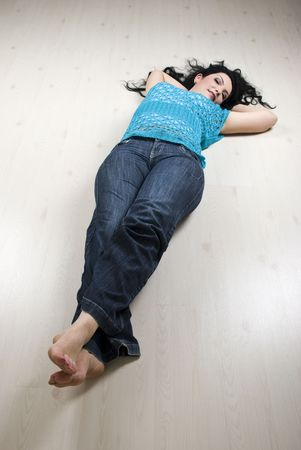 lay down: Beautiful woman resting on white laminate flooring barefoot