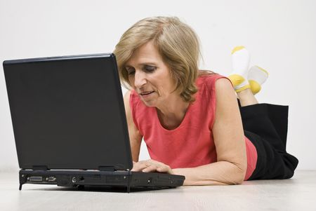 Senior woman relaxing  on floor and browsing internet on laptop photo