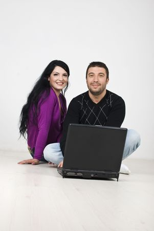 Smiling young couple sitting on floor with laptop and planning in their new house,coupy space for text message photo