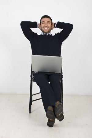 Happy  business man sitting on chair in a relaxed position with hands under head and holding a laptop Stock Photo - 6836880