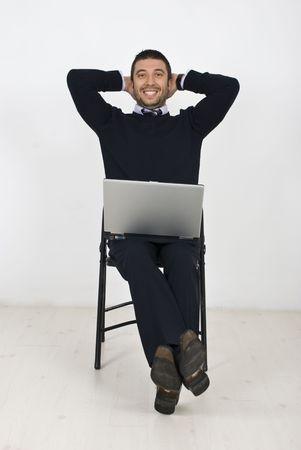 Hombre de negocios feliz sentado en la silla en una posición relajada con las manos en la cabeza y sosteniendo un ordenador portátil  Foto de archivo - 6836880