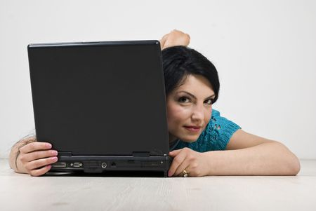 Young woman lying down on floor and looking behind laptop photo