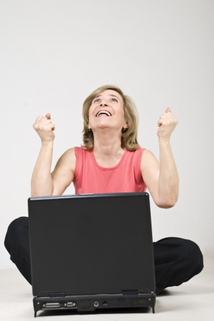 Excited senior woman sitting on floor with laptop and having a success in business photo