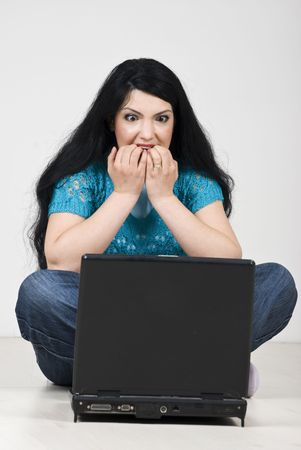 Stressed woman  looking scared and biting her nails in front of laptop photo