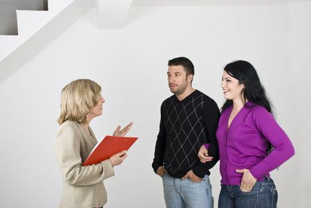 Young couple having a meeting with a senior estate agent and she showing them a new house photo