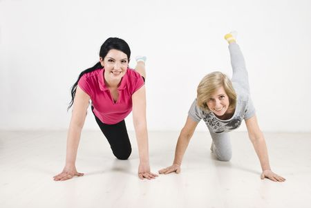 Two women in a good shape training on wooden floor  photo