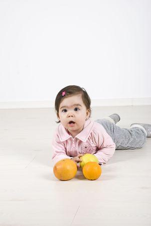 girl lying down: Chica de ni�o acostado sobre el laminado de suelos y jugando con frutas