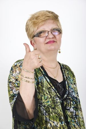 Smiling blond mature woman  with glasses giving thumbs up photo