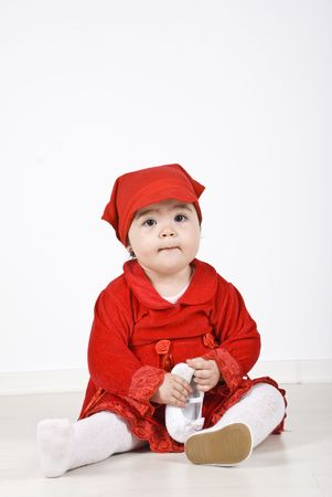 Little girl 11 months old sitting on floor dressed in  little red riding hood  costume and holding a shoe in her hands photo