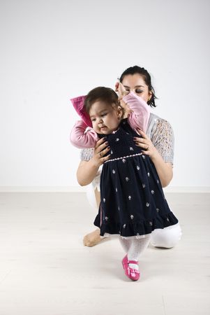 Young mother holding her little girl  helping to do first dance steps photo